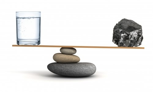 A full glass of water being balanced against a lump of coal